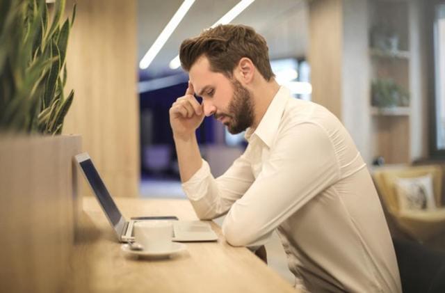 パソコンを見ながら悩む男性