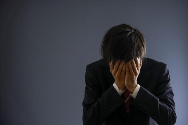 頭を抱えて後悔する男性